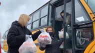 Lisbon staff loading a school bus with food for students